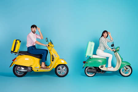 Full body profile photo of shocked lady guy drive two retro moped rush hour suitcases fixed behind travelers taking off sun glasses formalwear outfit isolated blue color background