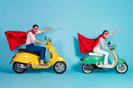 Full length profile photo of crazy lady guy drive two retro moped raise fists wear red cape cloak mask rushing road party super heroes role coat fly air isolated blue color background