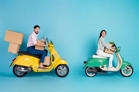 Full length photo astonished man woman bikers drivers get property mortgage drive motor bike carry papercard packages lamp flower wear formalwear outfit isolated blue color background