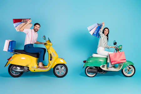 Full size profile side photo two people wife husband driver biker drive motor bike transport store mall many bags bought wear formalwear shirt pants trousers isolated blue color background