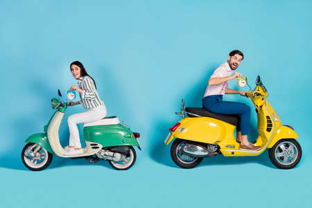 Full body profile side photo funny funky wife husband couple drive motor bike enjoy fast speed route adventure check time on clock bell wear shirt trousers isolated blue color background