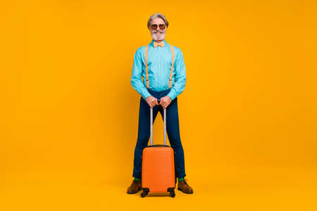 Full size photo of cool grandpa hold rolling suitcase luggage registration table airport wear sun glasses shirt suspenders bow tie pants boots socks isolated yellow color background