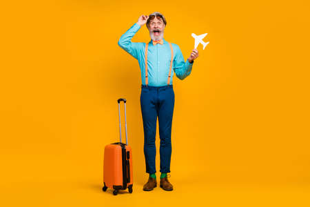 Full body photo of crazy grandpa hold paper plane travel rolling suitcase open mouth wear sun specs blue shirt suspenders bow tie pants boots socks isolated yellow color background