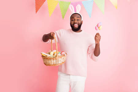Photo of funny dark skin guy easter party hold festive basket ginger bread cookies painted eggs sticks wear sweater pants bunny ears colorful flags hang pink color background Stock Photo