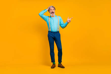 Full length photo of cool trendy grandpa charismatic person stylish look direct finger empty space wear shirt suspenders bow tie pants boots socks isolated yellow color background