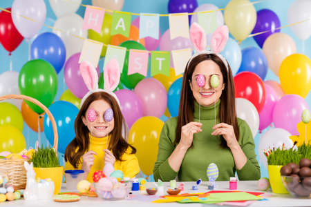 Portrait of nice attractive lovely funny glad cheerful cheery girls having fun covering eyes with festal decor eggs fooling enjoying festive good mood