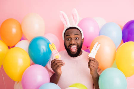 Photo of funny dark skin guy colorful decorations easter party hold two pretty, ginger bread cookies wear sweater bunny ears on balloons pink color background