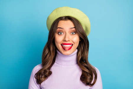 Closeup photo of pretty lady sticking tongue out mouth good mood red lips childish person wear green beret hat purple turtleneck isolated blue color background