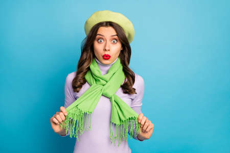 Photo of funky traveler lady holding scarf hands not sure about style want change clothes wear green beret hat purple turtleneck isolated bright blue color background
