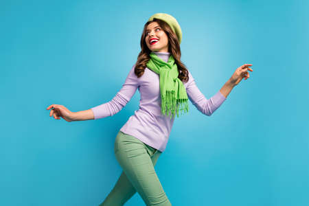 Low below angle view profile photo of charming pretty lady traveler walk street excited mood wear green beret hat purple jumper scarf pants isolated blue color background