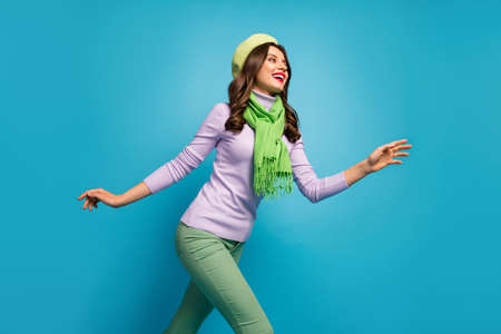 Low angle view profile photo of charming pretty lady traveler walk street excited mood wear green beret hat purple jumper scarf pants isolated blue color background