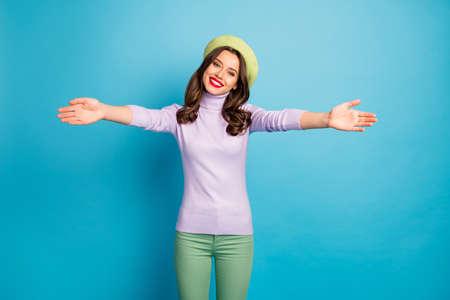 Photo of funny traveler lady good mood open hugs meet best friend airport wear modern green beret hat purple turtleneck jumper pants isolated blue color background