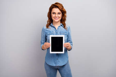 Portrait of positive woman promoter hold tablet present new device ads promo suggest select wear good look clothes isolated over grey color background