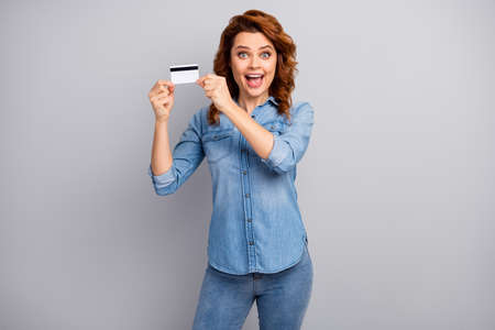 Look i get golden card. Astonished crazy woman hold credit bank impressed by online debit payment service scream wow omg wear style stylish trendy clothes isolated grey color background