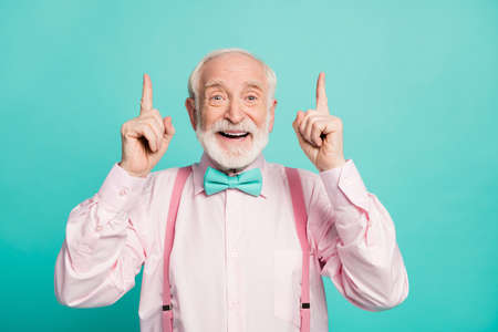 Portrait of amazed excited old man point index finger up recommend suggest select ads promo sales wear pink shirt bowtie isolated over turquoise color background