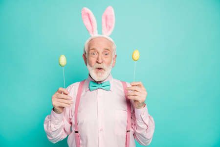 Portrait of astonished grandfather man celebrate easter party hold colorful eggs stick he get from his grand kids impressed scream wow omg wear pink shirt isolated teal color background
