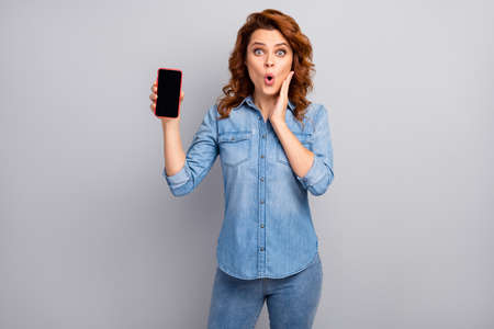 Portrait of astonished crazy woman hold smartphone show new device impressed scream unbelievable unexpected wear good look outfit isolated over grey color background Foto de archivo