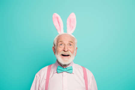 Portrait of crazy excited energetic old man look up copyspace impressed incredible discounts scream wow omg wear bowtie hare headband pink clothes isolated over teal color background Banque d'images