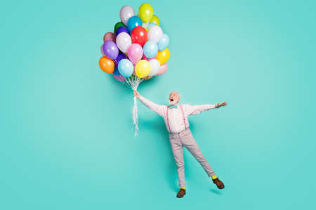 Full length photo amazed excited pensioner man hold many helium balloons flying wind sky he impressed scream wow omg wear pink grey pants trousers brown shoes isolated teal color background