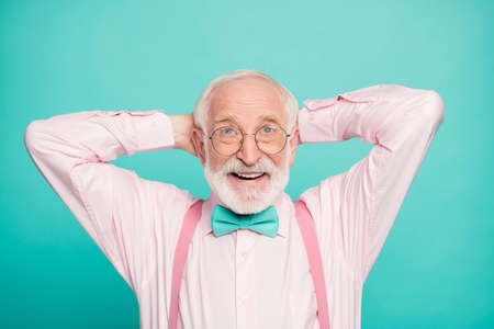 Closeup photo of funny grandpa positive facial expression good mood hands behind head look up empty space wear specs pink shirt suspenders bow tie isolated bright teal color background