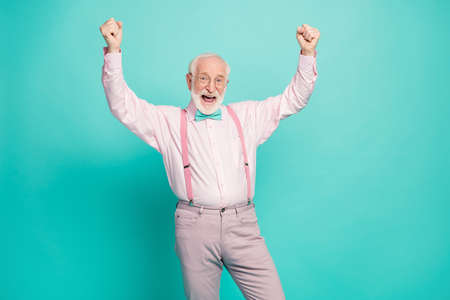 Photo of funny attractive crazy excited grandpa raise fists up celebrating money income wear specs pink shirt suspenders bow tie pants isolated teal color background Banque d'images