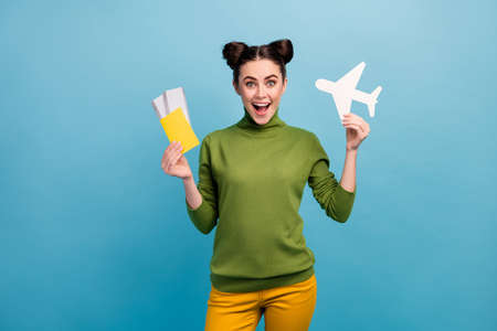 Photo of funny excited lady hold paper air plane passport tickets addicted traveler buy cheap tour abroad wear green turtleneck yellow trousers isolated blue color background