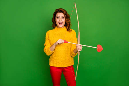 Photo of pretty lady hold cupid love arrows bow shoot aiming loving hearts theme party character wear yellow knitted sweater red trousers isolated green color background