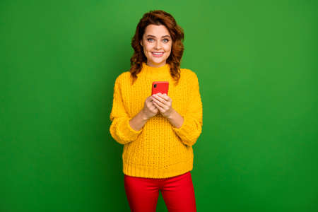 Portrait of positive cheerful addicted woman use smartphone enjoy chatting with social media friends wear style trendy pullover isolated over bright shine color background