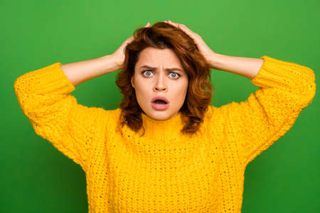 I cant do that. Frustrated shocked nervous woman hear unbelievable news her work mistake puzzled touch hands head scream wear good look knitted sweater isolated green color background