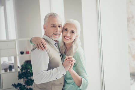 Close up photo of lovely old people looking dressed shirt brown turquoise pullovers standing in light apartment