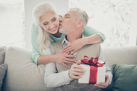 Portrait of cute married people have anniversary party wearing teal jumper kissing sitting cozy couch in apartment