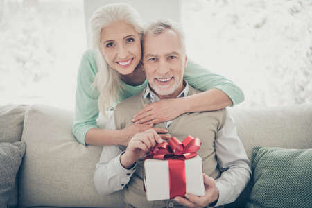 Portrait of charming spouses in pullover opening package for 14-february sitting divan apartment room Banque d'images