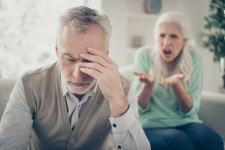Close up photo of upset sad tired exhausted man touching head having headache from the voice of his aggressive wife Banque d'images