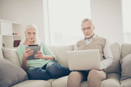 Photo of interested grandma using electronic gadget enjoying fresh news on site and smart granddad wearing specs typing e-mail to friends they are sitting on soft divan