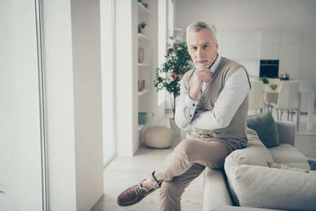 Photo of white haired aged man waiting client picking cool pose leaning sofa indoors