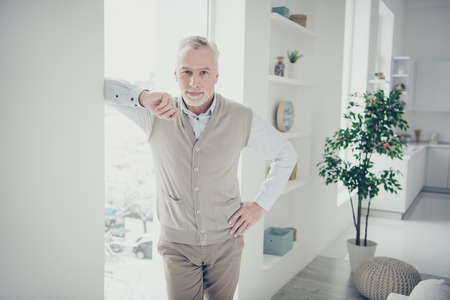 Photo of white haired aged man waiting client for renting house leaning window indoors Stok Fotoğraf
