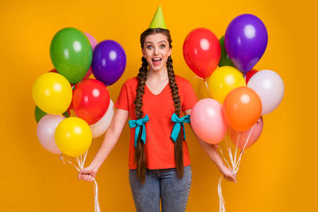 Surprise. Photo of cheerful pretty funny lady hold many air balloons hands birthday party best friend wear paper cone cap casual red t-shirt jeans isolated bright yellow color background
