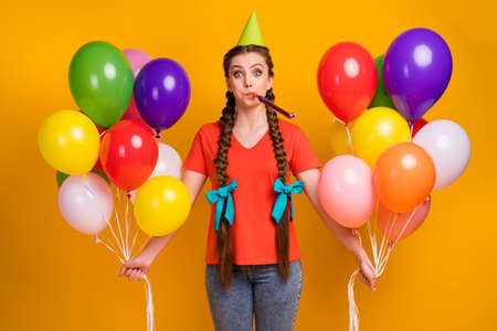 Photo of attractive funny lady hold many air balloons hands birthday party best friend blow noisemaker wear paper cone cap casual red t-shirt jeans isolated vibrant yellow color background