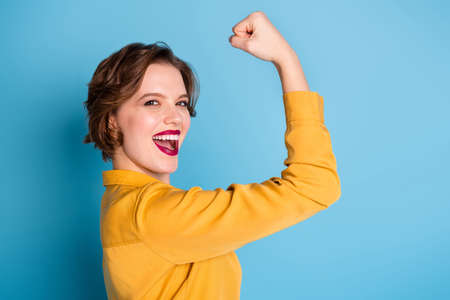 Profile photo of pretty cheerful lady hold raise biceps hand arm show, perfect biceps gym training strong powerful woman wear yellow shirt isolated bright blue color background Фото со стока