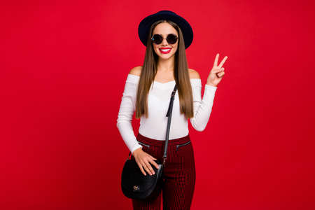 Portrait of positive cheerful girl in sunglass headwear rest relax, make-v-sign wear good look plaid pants isolated over bright shine color background Фото со стока