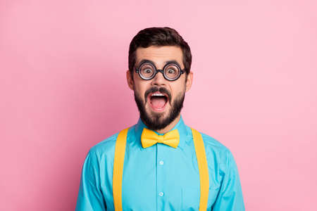 Close-up portrait of his he nice attractive funky overjoyed comic cheerful cheery crazy bearded guy nerd wearing thin specs opened mouth isolated over pastel pink color background