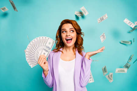 Shocked crazy professional woman hold money fan lottery earnings hold hand impressed dollars falling fluying wear violet formalwear jacket isolated teal turquoise color background