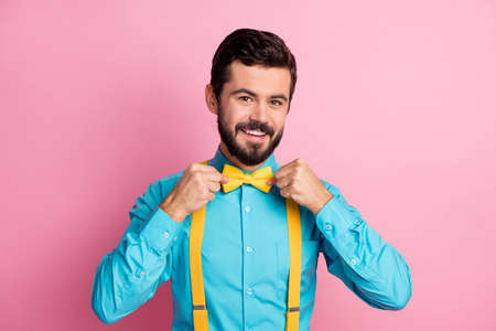 Close-up portrait of his he nice attractive cheerful cheery content imposing well-dressed bearded guy wearing festal mint blue shirt fixing bow-tie isolated over pastel pink color background