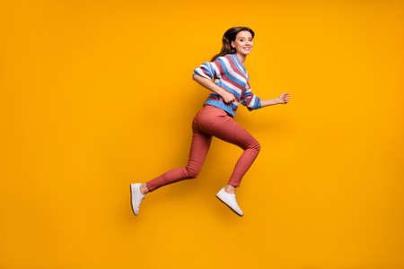 Full length profile side photo of cheerful girl jump run fast after spring discounts wear sweater sneakers isolated over shine color background Imagens