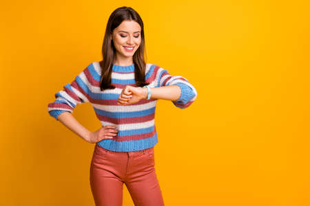 Portrait of her she nice-looking attractive lovely charming pretty cheerful cheery brown-haired girl looking at watch waiting meet isolated on bright vivid shine vibrant yellow color background