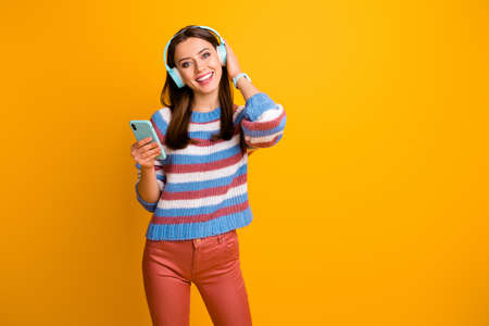 Portrait of her she nice attractive lovely cute cheerful cheery brown-haired girl holding in hands mp3 player listening stereo sound rock isolated on bright vivid shine vibrant yellow color background Stock fotó