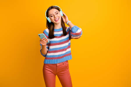 Portrait of her she nice attractive dreamy cheerful brown-haired girl listening stereo radio hit pop rock jazz soul modern isolated over bright vivid shine vibrant yellow color background
