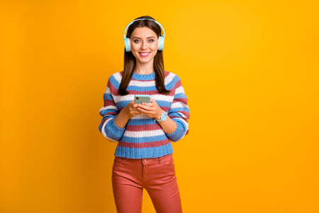 Portrait of her she nice attractive lovely pretty cheerful cheery brown-haired girl holding in hands mp3 player listening new track isolated over bright vivid shine vibrant yellow color background Stock fotó