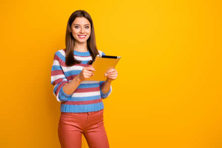Portrait of her she nice attractive lovely pretty cute cheerful cheery brown-haired girl holding in hands using ebook app isolated over bright vivid shine vibrant yellow color background