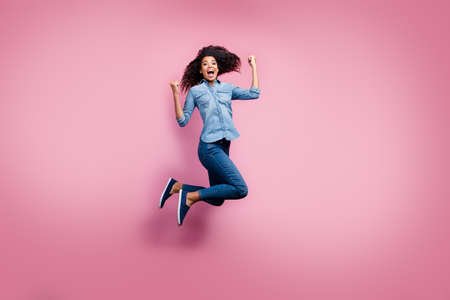Full body photo of delighted afro american girl hear lottery win news impressed scream yeah jump raise fists feel euphoria emotions wear casual style outfit isolated pink color background